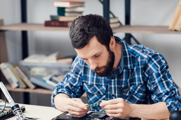 ひげを生やしたエンジニアがマイクロ回路を調べる