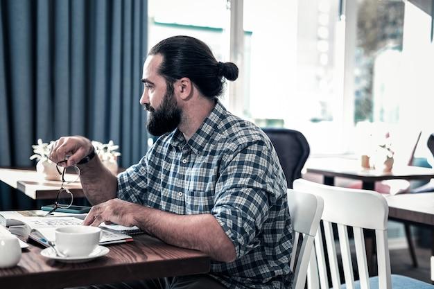 ひげを生やした起業家。レストランに座って本を読んで四角いシャツを着ているひげを生やした黒髪の起業家