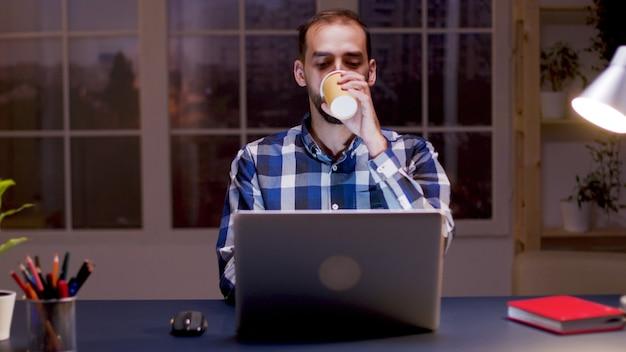 ひげを生やした起業家がコーヒーを一口飲んで、夜の時間帯にホームオフィスのコンピューターで作業しています。