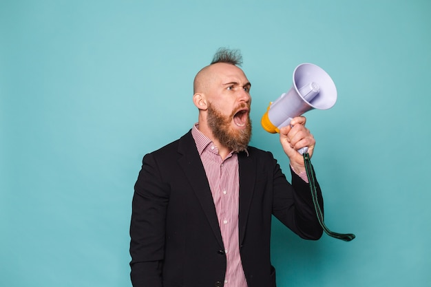 Bearded european businessman in dark suit isolated, with megaphone shouting with serious angry face, asking for attention
