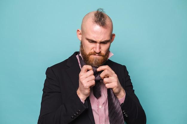 孤立した暗いスーツを着たひげを生やしたヨーロッパのビジネスマン、ネクタイを結ぶことを試みて怒っているそれを行う方法がわからない