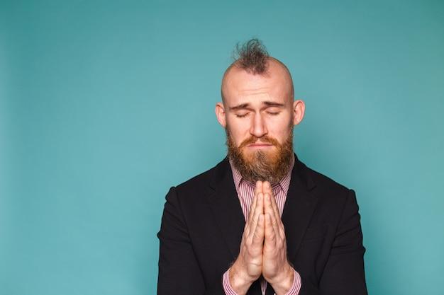 暗いスーツを着たひげを生やしたヨーロッパのビジネスマンは、非常に感情的で心配している顔の希望の表現と一緒に手で物乞いと祈りを孤立させました