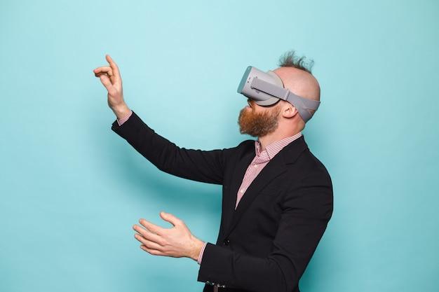 暗いスーツを着たひげを生やしたヨーロッパのビジネスマンは、仮想現実の眼鏡をかけて孤立した、興奮した驚きのタッチ空気