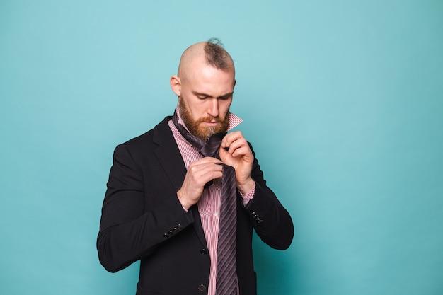 孤立した暗いスーツのひげを生やしたヨーロッパの実業家、ネクタイを結ぶ