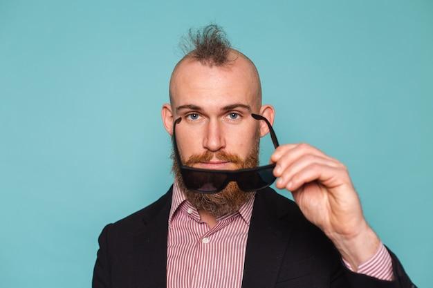 サングラスをかけて、孤立した暗いスーツのひげを生やしたヨーロッパの実業家