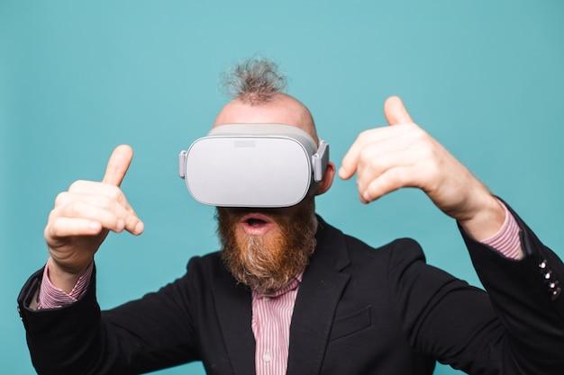Бородатый европейский бизнесмен в темном костюме изолирован, в очках vr на голове с возбужденным изумленным потрясенным лицом с открытым ртом