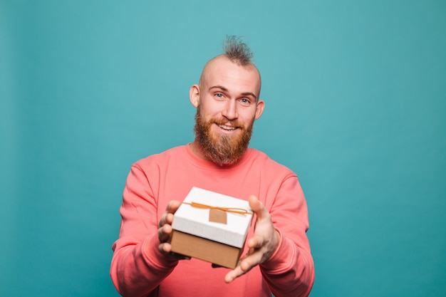 Bearded european man in casual peach isolated, happy holds out gift box