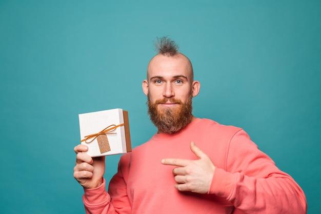 캐주얼 복숭아 절연에 수염 된 유럽 남자, 흥분된 쾌활한 지주 선물 상자