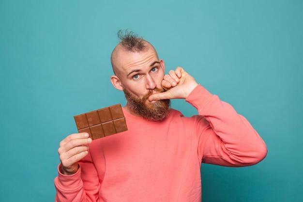 고립 된 캐주얼 복숭아에 수염 된 유럽 남자, 맛있는 초콜릿 핥는 손가락을 들고