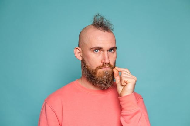 캐주얼 복숭아 절연, 입과 입술에 수염이 난 유럽 남자가 손가락으로 지퍼로 닫힙니다.