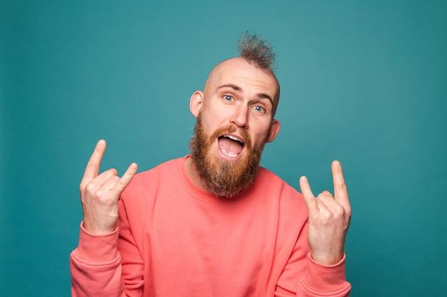 Бородатый европейский мужчина в повседневном персиковом костюме, кричащий с сумасшедшим выражением лица, делает рок-символ с поднятыми руками