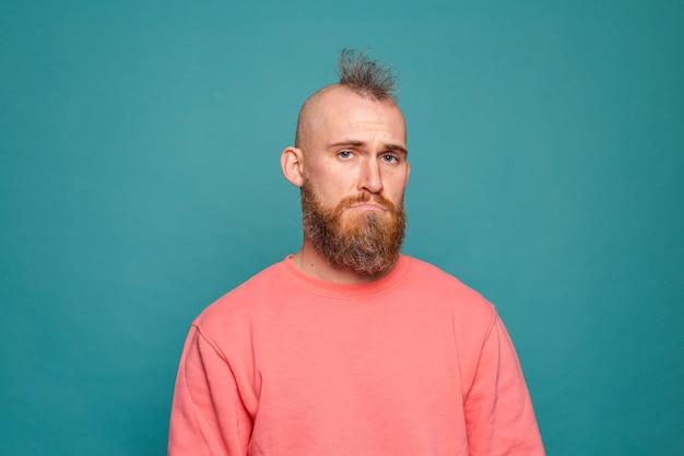 Бородатый европейский мужчина в повседневном персиковом костюме с мрачным выражением лица нуждается в поддержке и помощи