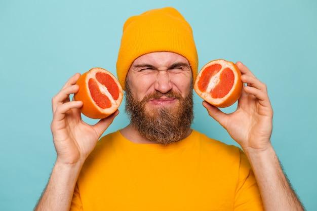 分離された黄色いシャツのひげを生やしたヨーロッパ人、グレープフルーツの味、苦味からのしわ