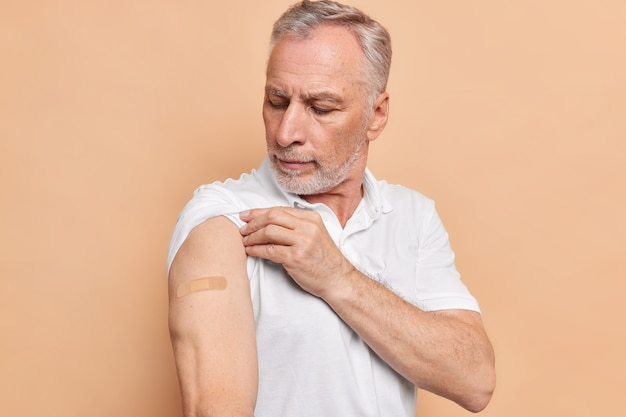 수염 난 유럽 남성은 베이지색 벽에 격리된 흰색 티셔츠를 입고 안전하고 효과적인 코로나바이러스 백신에 만족한 석고로 팔을 쳐다본다