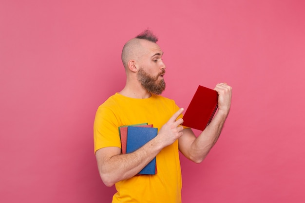 Barbuto uomo europeo con una pila di libri in rosa