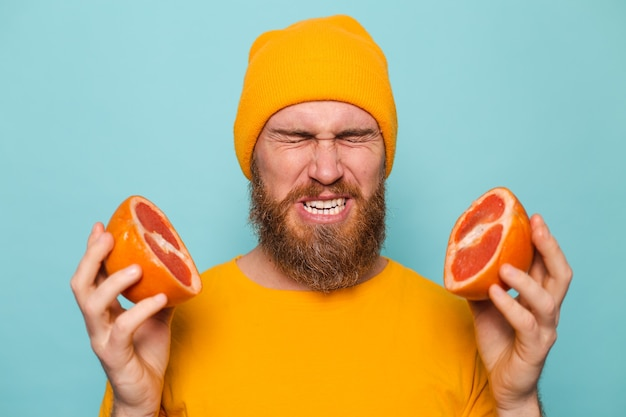 Bearded european man in yellow shirt isolated, holding grapefruit tastes, wrinkles from bitterness