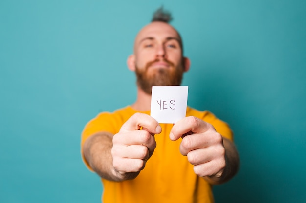Bearded european man in yellow shirt isolated, holding yes with surprise and amazed expression excited face.