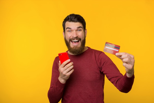 Bearded excited guy, using mobile phone and showing at camera crdit card, standing over yellow background