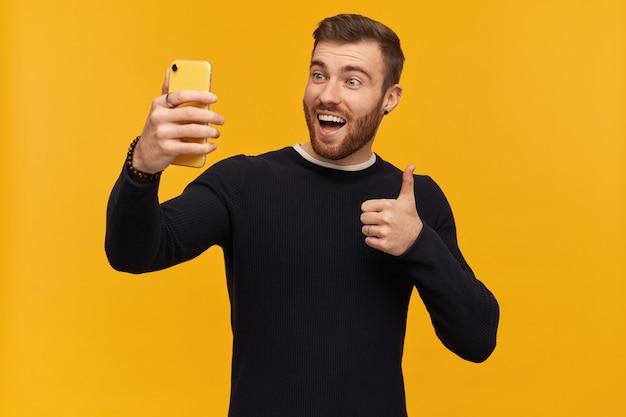 ブルネットの髪のひげを生やした興奮した、幸せそうな男。ピアスあり。黒のセーターを着ています。自撮り写真を作成し、親指を立てるサインを表示し、ジェスチャーを承認します。黄色い壁の上に隔離されたスタンド