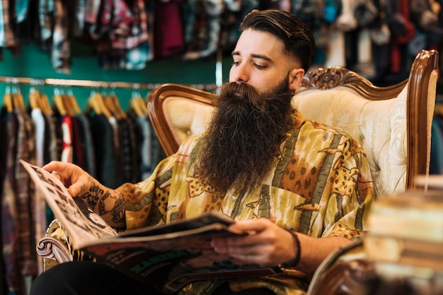 Bearded fashionable young man sitting on chair looking at magazine in the shop