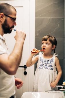 Бородатый отец и его маленькая дочь чистят зубы в ванной и смотрят друг на друга. мужчина учит свою дочь чистить зубы.
