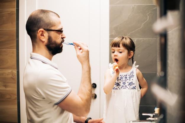 Бородатый отец и его маленькая дочь чистят зубы в ванной комнате. мужчина учит свою дочь чистить зубы.