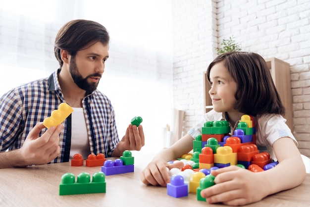 Bearded father asks son to share toy colored blocks.