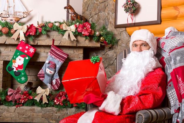 Бородатый дед мороз в красном костюме с подарочной коробкой, сидя в кресле, у камина и праздничным украшением