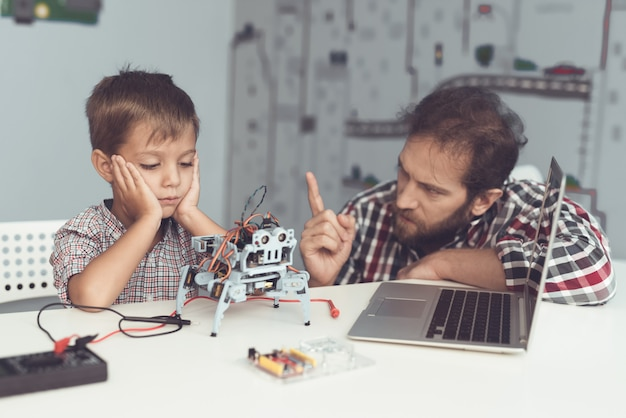 Bearded father help upset son with robot at home.