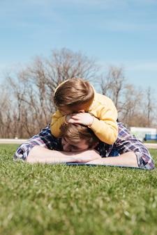 Il padre barbuto si trova all'aperto con suo figlio nel parco