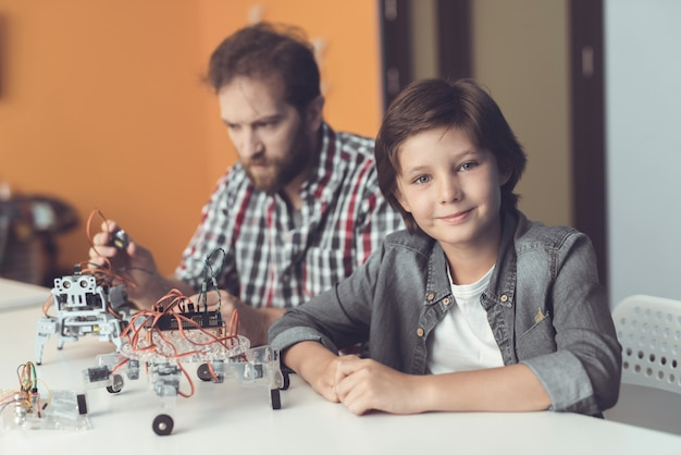Bearded father and son constructing robot at home.