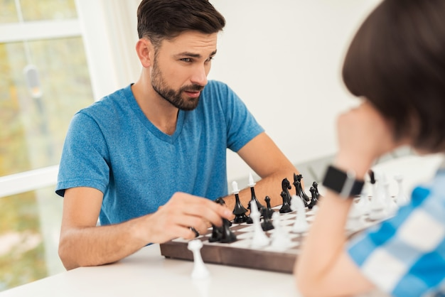 Bearded father and son playing chess on table.