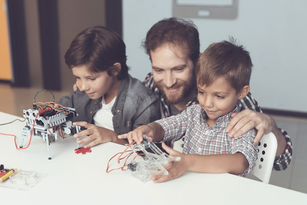 Bearded father and sons constructing robot at home
