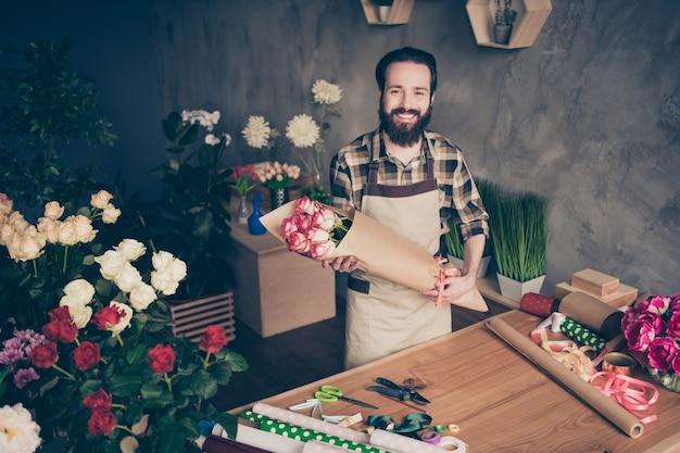 Бородатый флорист работает в своем цветочном магазине