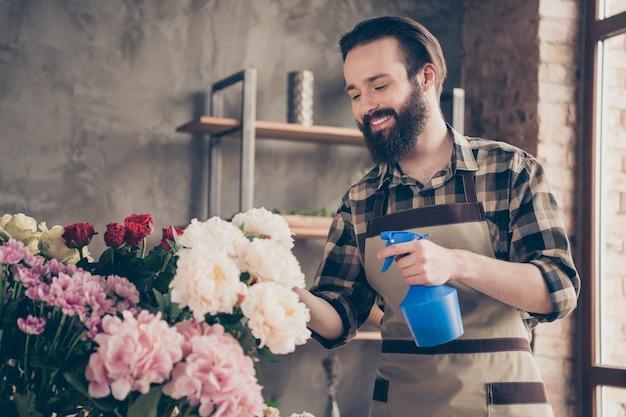 彼のフラワーショップで働いているひげを生やした花屋