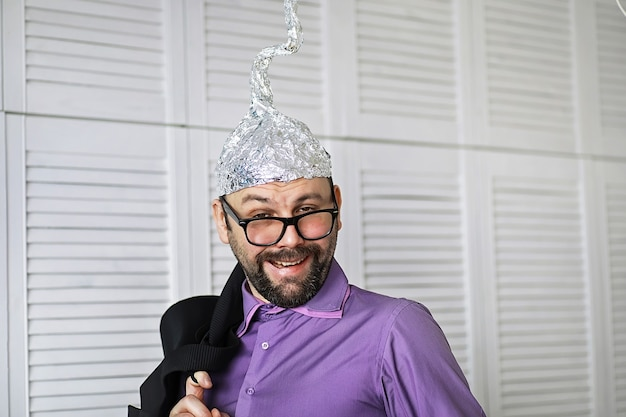 Бородатый забавный человечек в кепке из алюминиевой фольги. фобии концепт-арта. теория заговора. заговор. безумие.