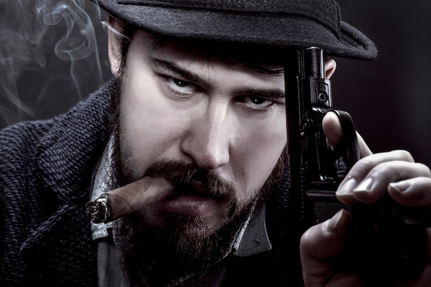 Bearded gangster in a hat with a gun in his hand and a cigarette in his mouth on black wall