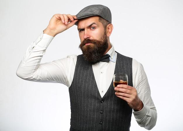 Бородатый господин пьет коньяк. потягивая лучший виски. портрет мужчины с густой бородой. мачо пьёт. стильный богатый человек, держащий стакан старого виски.