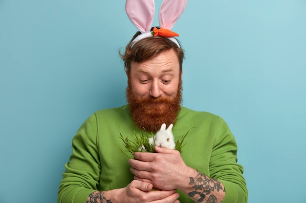 Bearded ginger man with bunny ears feeds white fluffy rabbit