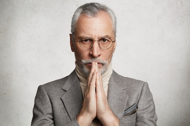 Bearded grey-haired elderly man wearing formal suit