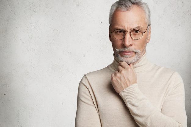 Bearded grey-haired elderly man wearing turtleneck