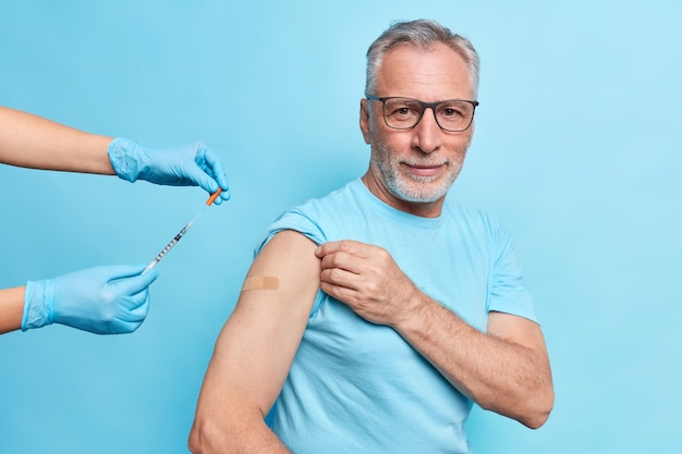 Bearded grey haired european man gets inoculation against coronavirus disease wears spectacles and t shirt isolated over blue wall