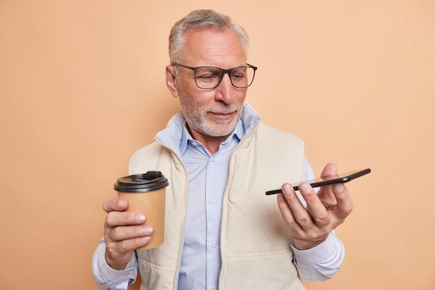 L'uomo anziano barbuto dai capelli grigi guarda attentamente i nuovi smartphone esamina i nuovi gadget