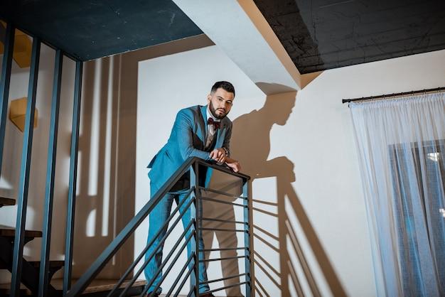 스튜디오에서 배경에 신부를 기다리는 수염된 신랑. 결혼식 날 부자 신랑. 흰 셔츠와 파란 양복을 입은 우아한 신랑