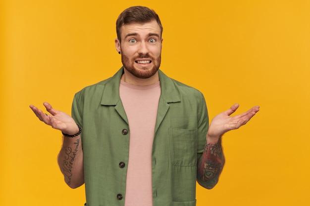 수염 난 남자, 갈색 머리를 가진 당황한 찾고 남자. 녹색 반팔 재킷을 입고. 문신이 있습니다. 어깨를 으쓱하고 확실하지 않은 제스처를 보여줍니다. 노란색 벽 위에 절연