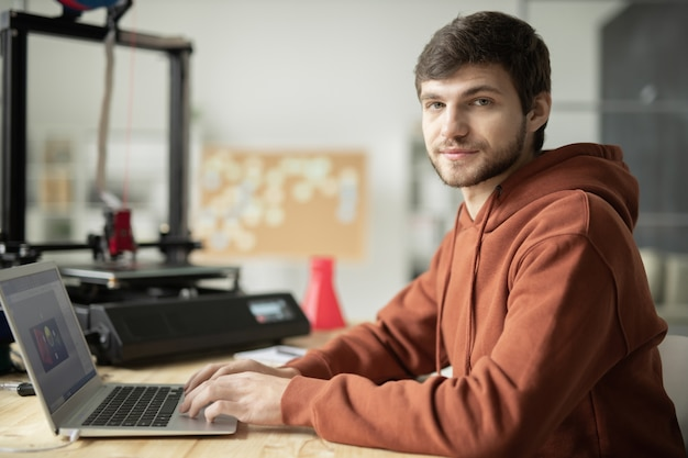 Bearded guy in brown hoodie sitting in front of laptop in office while working over sketches of items for 3d prirnting