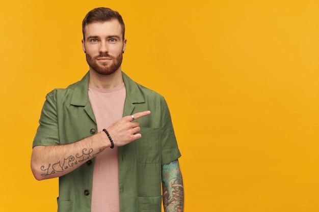 수염 난된 남자, 갈색 머리를 가진 자신감이 남자. 녹색 반팔 재킷을 입고. 문신이 있습니다. 노란색 벽 위에 고립 된 복사 공간에서 오른쪽으로 손가락을 가리키는