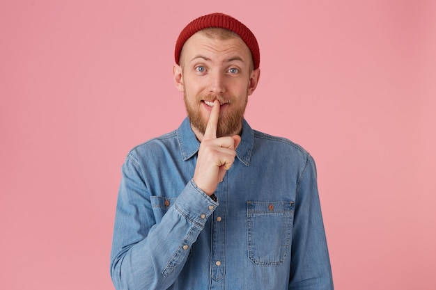 Bearded guy in denim shirt smiling showing silence gesture, asks to keep secret putting fore finger on the lips, isolated