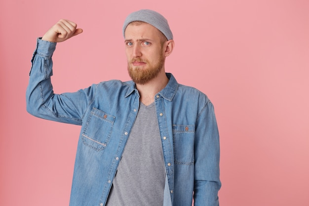 Bearded guy dressed in a denim shirt looks sad, can not boast of his strength, displeased with his physical form, raised his bent arm to demonstrate weak muscles, with chagrin looking