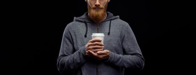 Бородатый парень пьет кофе с собой